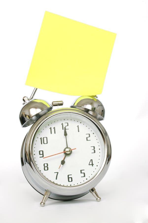 Reloj de alarma y nota imagen de archivo