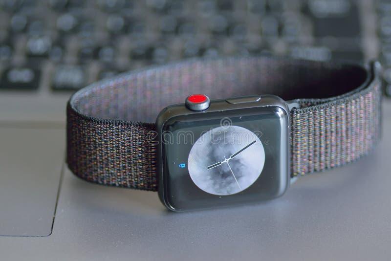 Reloj de Apple con el fondo borroso del teclado de la PC del ordenador portátil foto de archivo libre de regalías