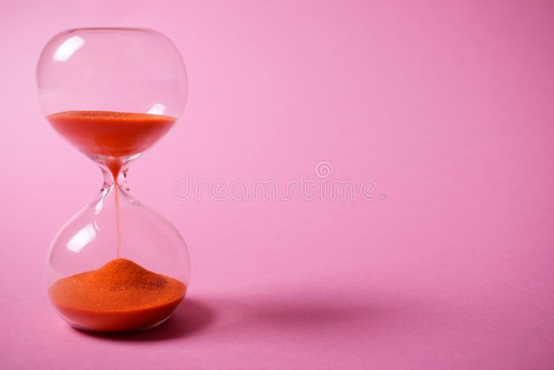 Reloj de arena con la arena anaranjada en fondo rosado fotos de archivo libres de regalías