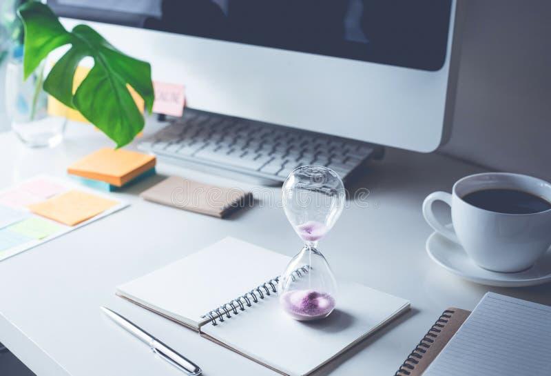 reloj de arena con la oficina de la mesa de trabajo Tiempo, concepto de la motivación fotografía de archivo