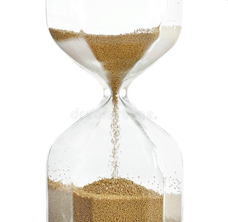 Reloj de arena con la arena que fluye en el fondo blanco Gestión de tiempo imagen de archivo