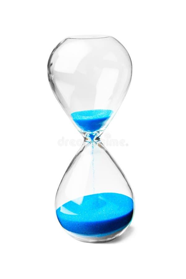 Reloj de arena de cristal con la arena azul aislada en el fondo blanco imagen de archivo