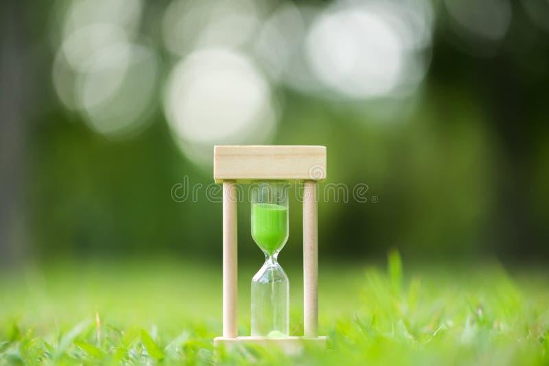 Reloj de arena en el campo de hierba verde, tiempo de primavera imagenes de archivo