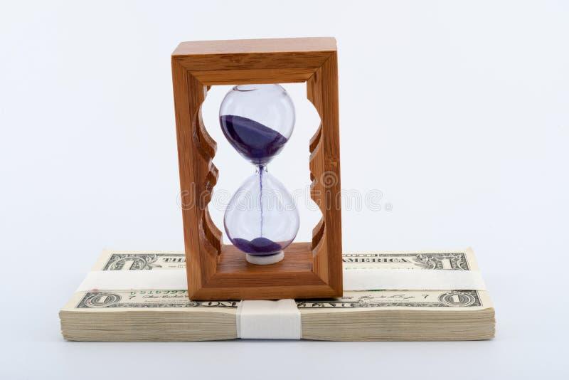 Reloj de arena en el dinero fotos de archivo libres de regalías