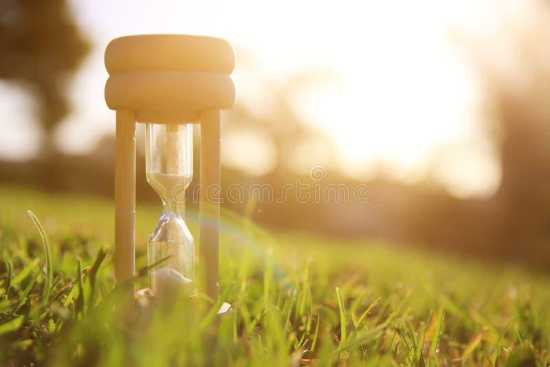Reloj de arena en el tiempo de la hierba durante puesta del sol Estilo de la vendimia fotos de archivo