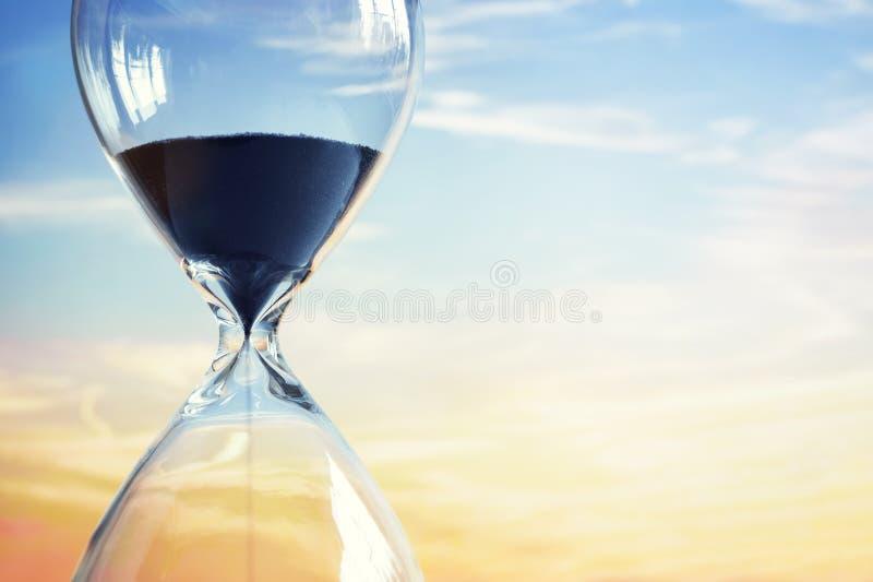 Reloj de arena en la puesta del sol imagen de archivo