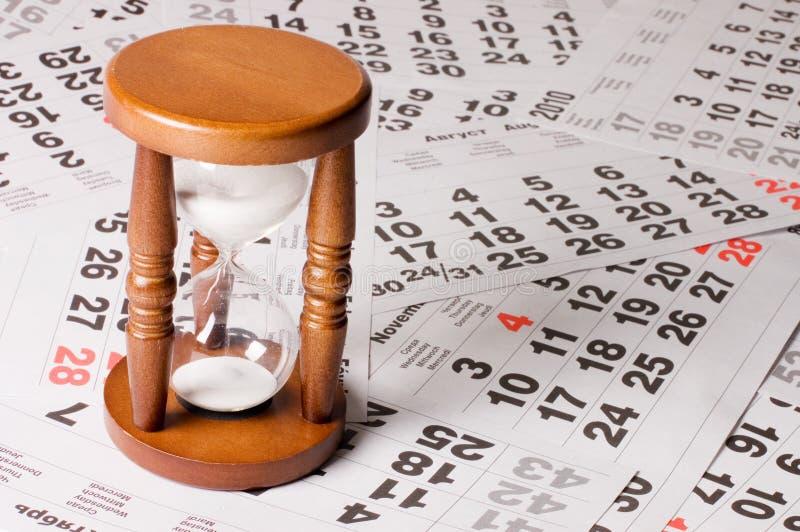 Reloj de arena en las hojas del calendario imagen de archivo