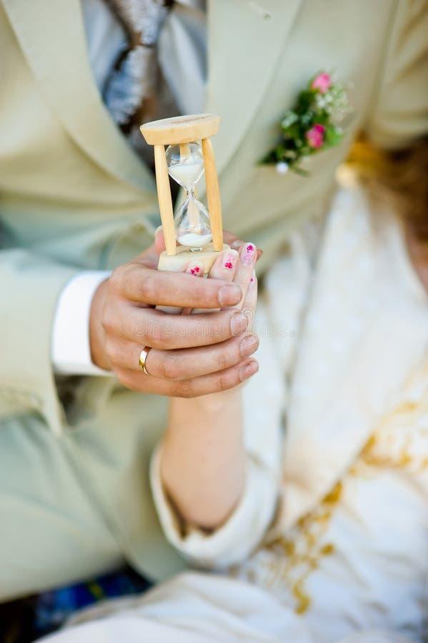 Reloj de arena en las manos del hombre y de la mujer fotografía de archivo