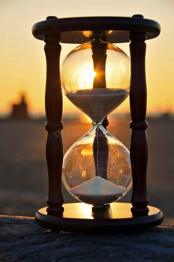 Reloj de arena en un registro en la puesta del sol fotografía de archivo libre de regalías