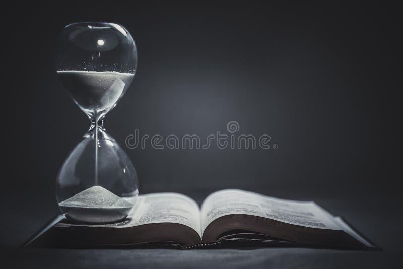 Reloj de arena en una biblia fotografía de archivo
