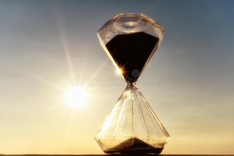 Reloj de arena en una puesta del sol del fondo fotos de archivo libres de regalías