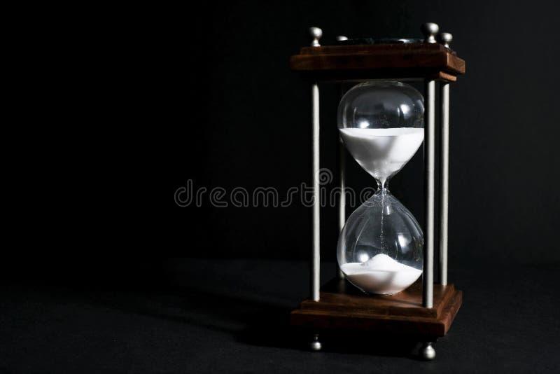 Reloj de arena, o reloj de la arena aislado en fondo negro, en li bajo imagenes de archivo