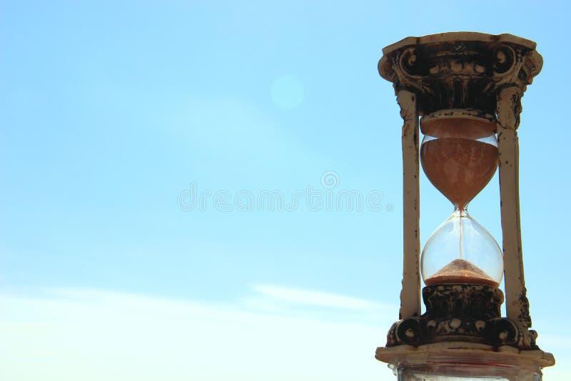 reloj de arena retro en el fondo del cielo azul y de las nubes blancas fotos de archivo