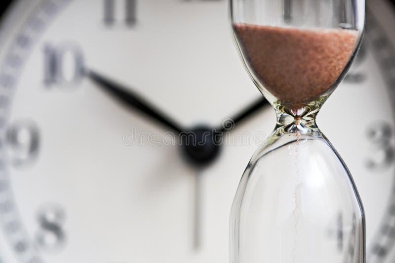 Reloj de arena y despertador viejo Reloj de la arena en el fondo del dial fotografía de archivo