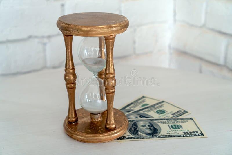 Reloj de arena y dinero de madera en un fondo blanco El concepto del tiempo es oro fotografía de archivo libre de regalías