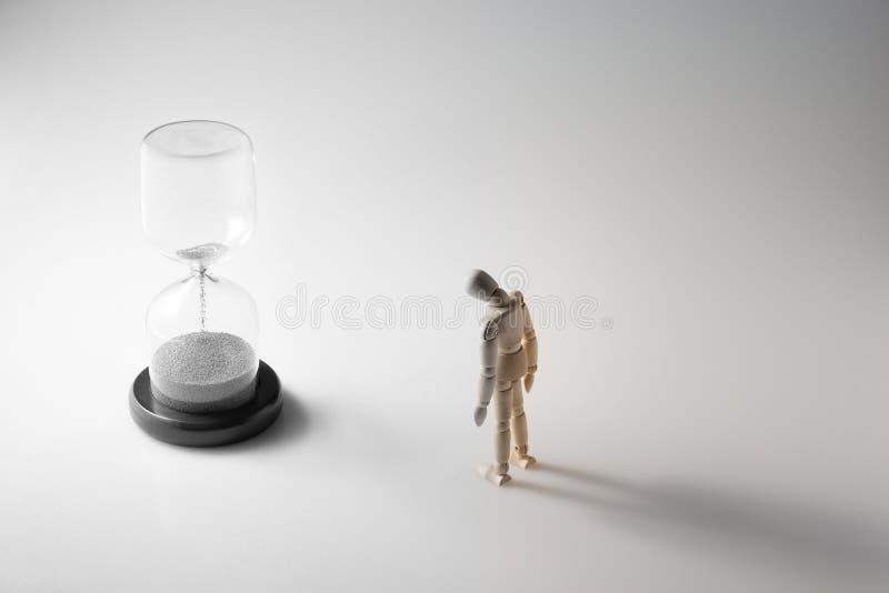 Reloj de arena y figura de madera turing el color gris del rato que se descolora como tiempo que corre hacia fuera fotografía de archivo