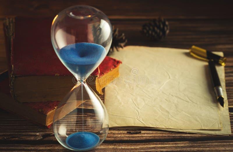 Reloj de arena y libros viejos con el papel y la pluma viejos imagenes de archivo