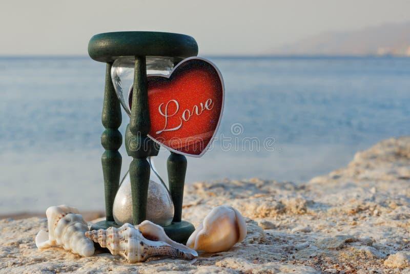 Reloj de arena y shelles en la playa marina fotografía de archivo