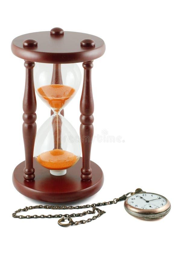 Reloj de arena y un reloj de bolsillo imagen de archivo