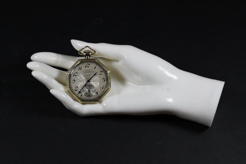 Reloj de bolsillo antiguo en mano del maniquí foto de archivo