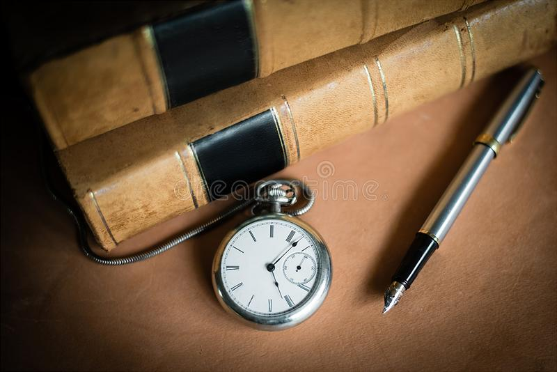 Reloj de bolsillo del siglo XIX con los libros encuadernados y la pluma de cuero imágenes de archivo libres de regalías