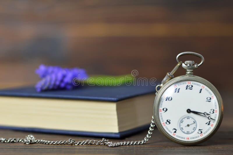 Reloj de bolsillo del vintage, libro y flores de la primavera imagen de archivo