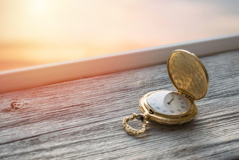 Reloj de bolsillo del vintage del oro con la luz de la puesta del sol en fondo de madera Contador de tiempo del reloj de arena o  foto de archivo