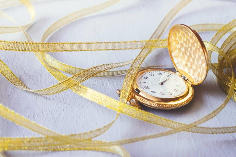 Reloj de bolsillo del vintage del oro con las cintas de oro en fondo gris del cemento Contador de tiempo del reloj de arena o de  foto de archivo libre de regalías