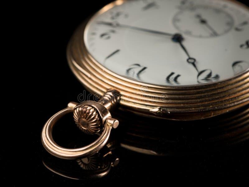 Reloj de bolsillo de oro viejo en una superficie reflexiva negra fotos de archivo