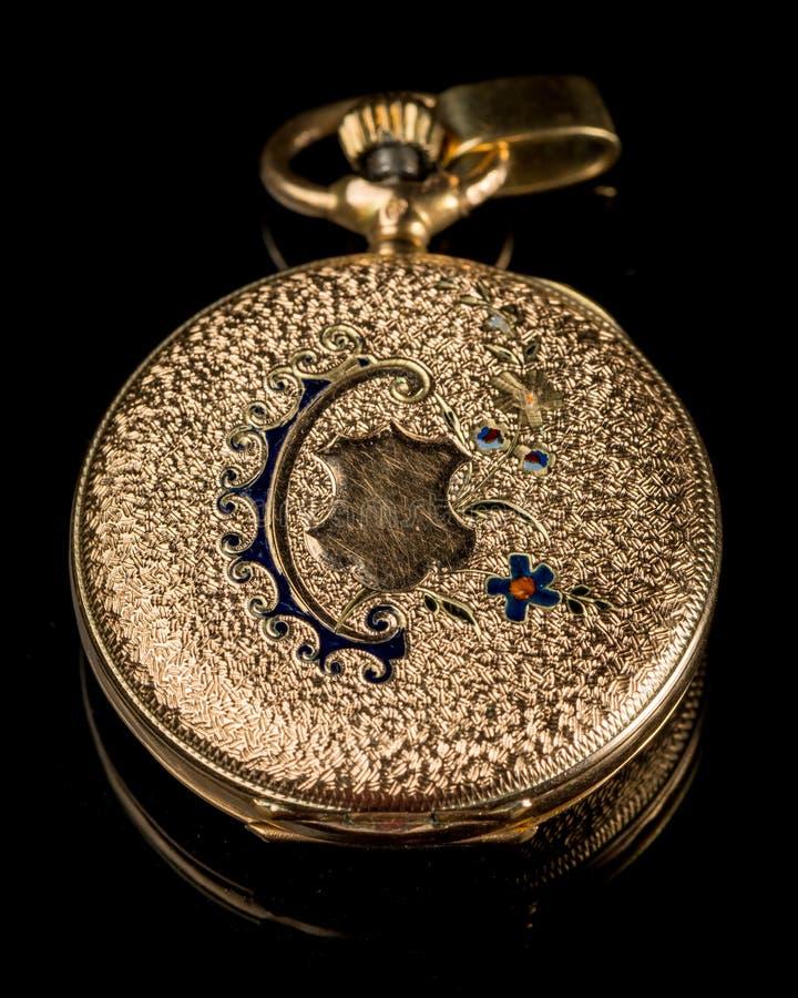 Reloj de bolsillo de oro viejo en una superficie reflexiva negra imagen de archivo libre de regalías