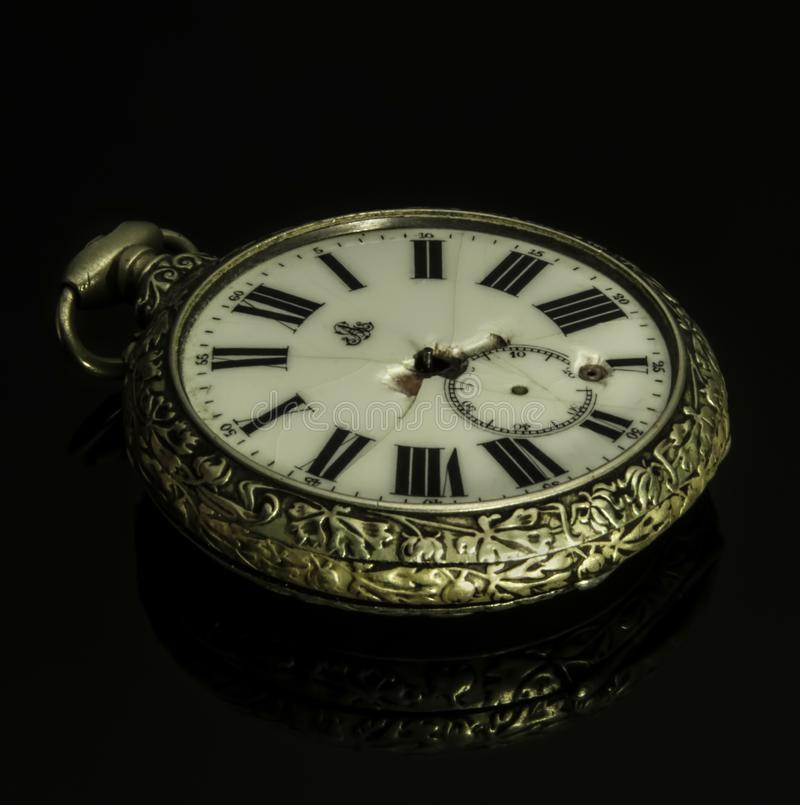 Reloj de bolsillo quebrado antiguo en fondo oscuro imagenes de archivo