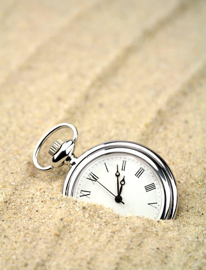 Reloj de bolsillo semi enterrado en la arena foto de archivo libre de regalías