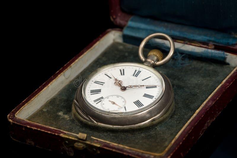 Reloj de bolsillo usado viejo en un caso en una superficie reflexiva negra imágenes de archivo libres de regalías
