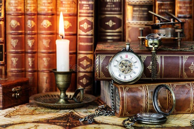 Reloj de bolsillo, vela ardiendo y libros viejos imagen de archivo