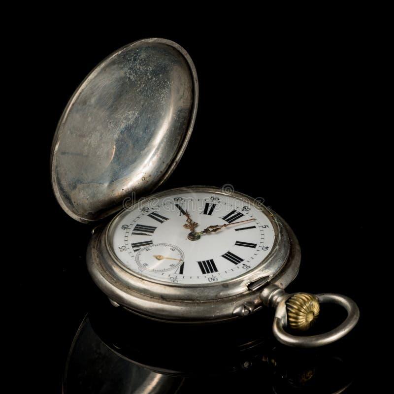 Reloj de bolsillo viejo en una superficie reflexiva negra, tapa abierta foto de archivo
