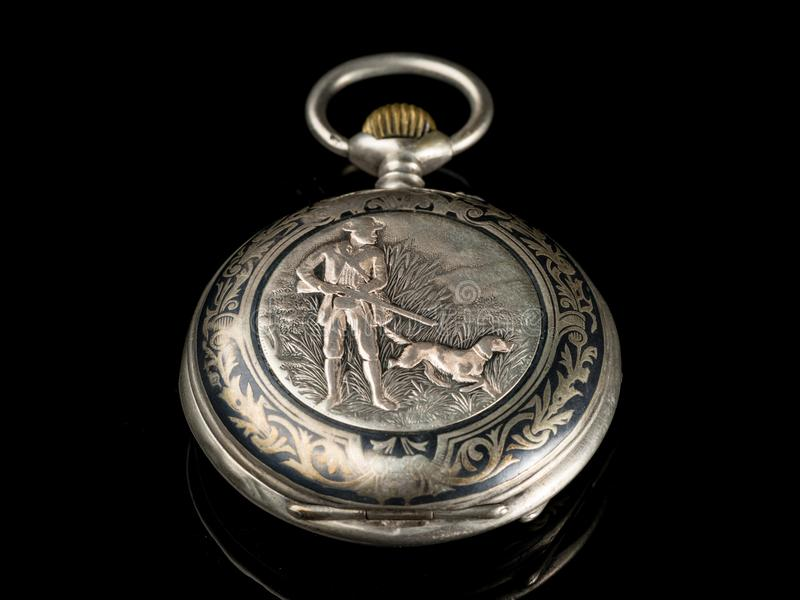 Reloj de bolsillo viejo en una superficie reflexiva negra, tapa cerrada con motivo de la caza imagen de archivo