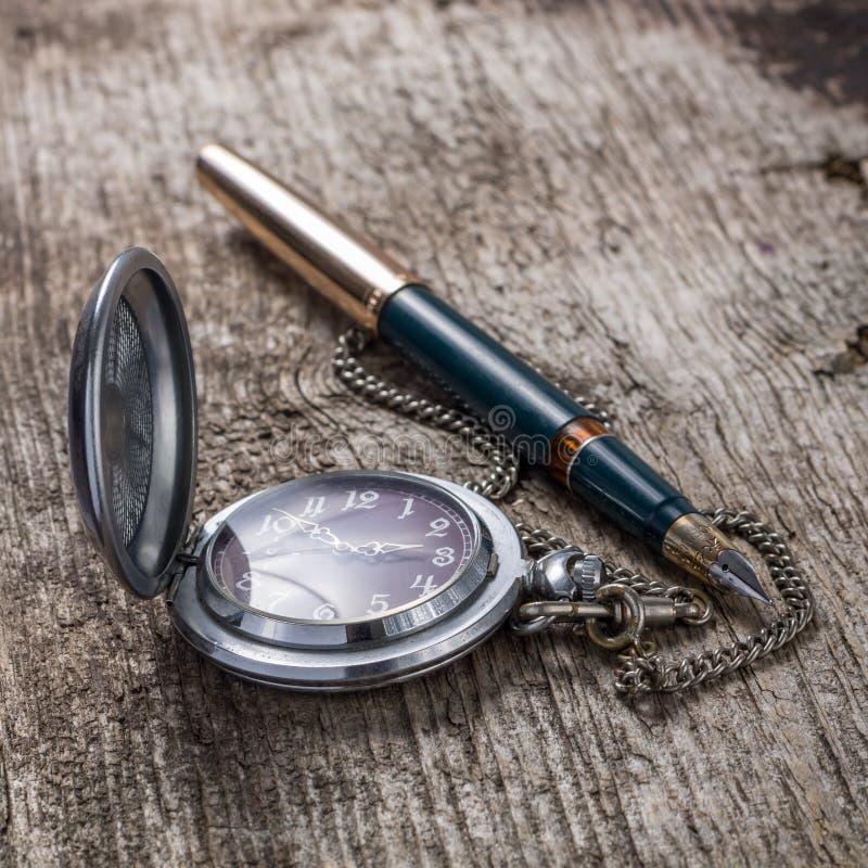 Reloj de bolsillo y pluma viejos en el fondo de madera imágenes de archivo libres de regalías