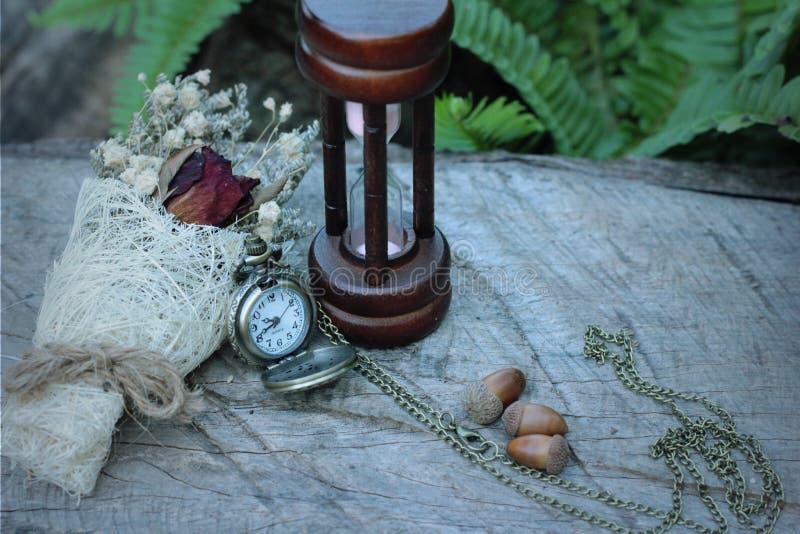 Reloj de bolsillo y reloj de arena antiguos con las flores secadas imágenes de archivo libres de regalías
