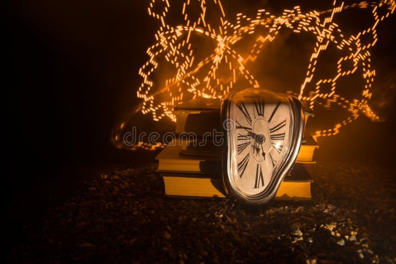 Reloj de fusión suave torcido en un banco de madera, la persistencia de la memoria de Salvador Dali foto de archivo