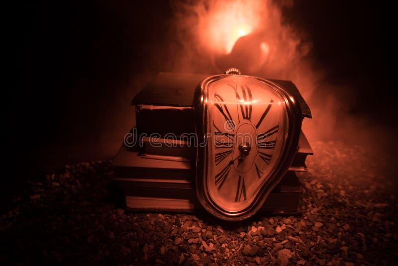 Reloj de fusión suave torcido en un banco de madera, la persistencia de la memoria de Salvador Dali imagenes de archivo