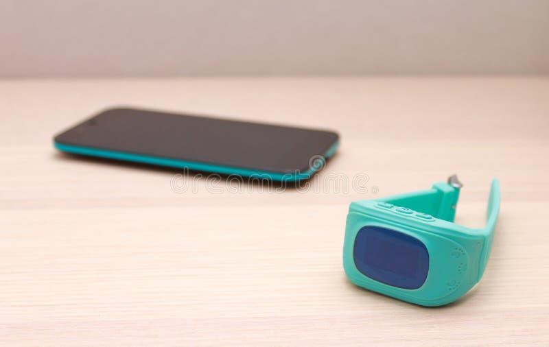 Reloj de GPS del niño y un teléfono elegante en el escritorio de madera fotos de archivo