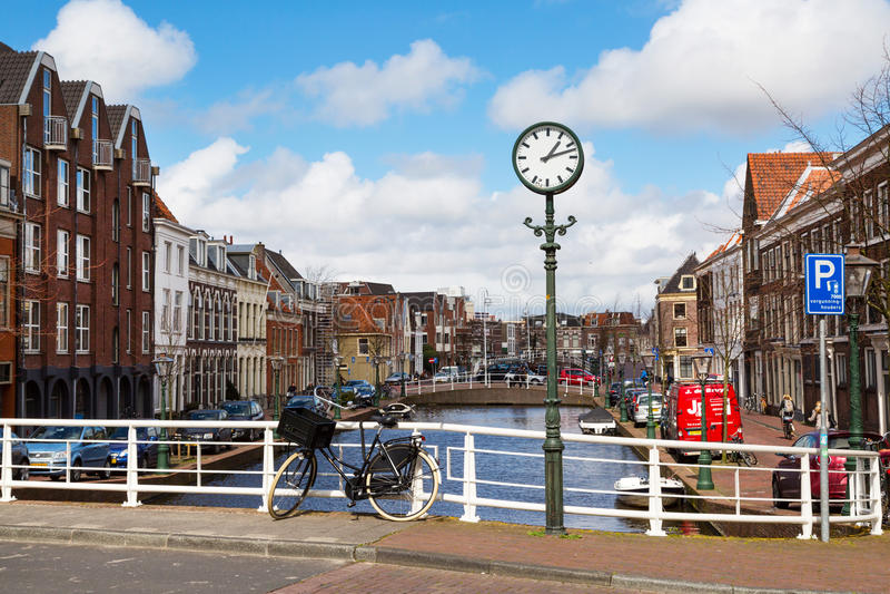 Reloj de la calle, puente, bici, casas tradicionales, canal en Leiden, Países Bajos imagen de archivo libre de regalías