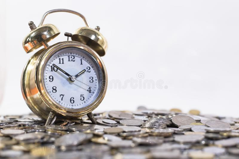Reloj de la campana de oro en un grupo de monedas fotografía de archivo libre de regalías
