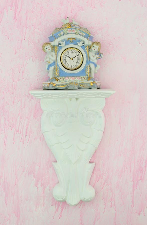 Reloj de la porcelana del vintage contra un fondo rosado foto de archivo libre de regalías