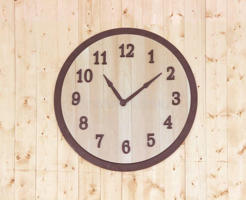 Reloj de madera en la pared de madera imágenes de archivo libres de regalías