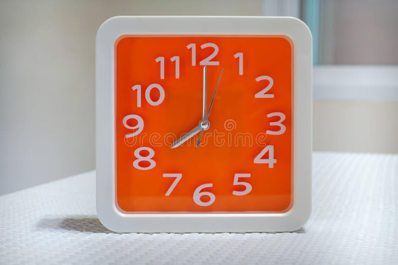 Reloj de pared anaranjado en la tabla blanca imagenes de archivo