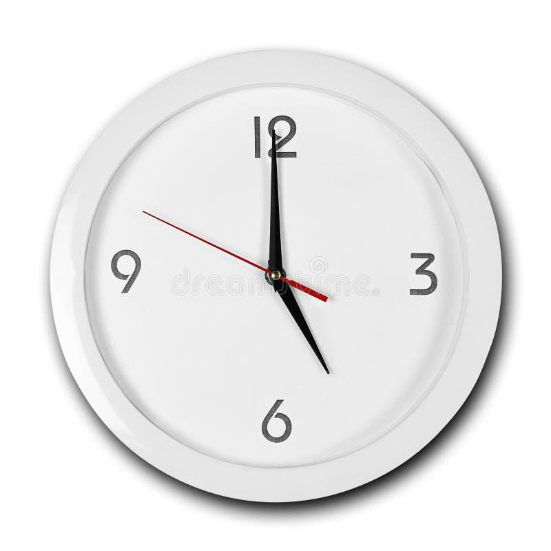 Reloj de pared blanco de la ronda grande con el marco blanco Las manos señalan a las 5 Cierre para arriba Aislado en el fondo bla foto de archivo