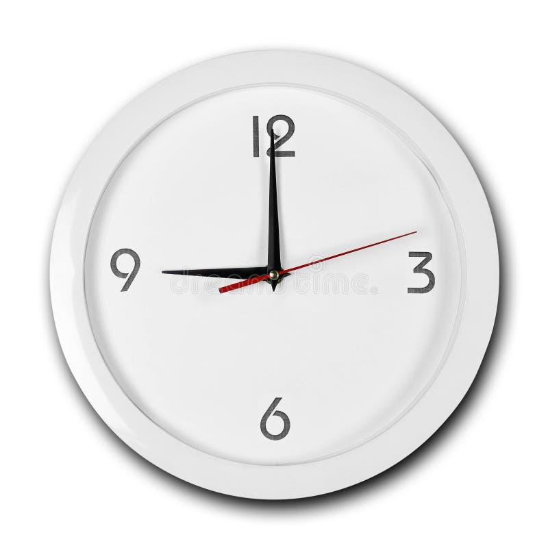 Reloj de pared blanco de la ronda grande con el marco blanco Las manos señalan a las 9 Cierre para arriba Aislado en el fondo bla imagenes de archivo
