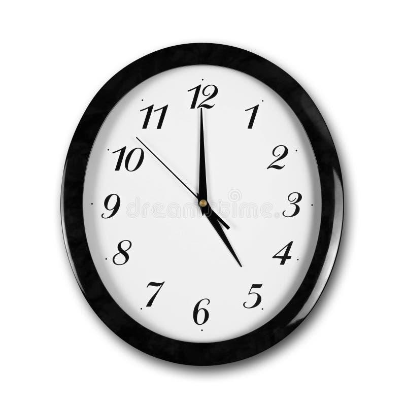 Reloj de pared blanco de la ronda grande con el marco negro Las manos señalan a las 5 Cierre para arriba Aislado en el fondo blan foto de archivo