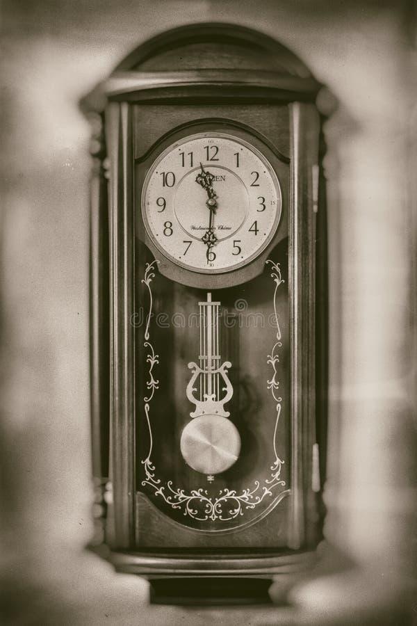 Reloj de pared viejo del vintage en la pared blanca en fondo en estilo de la sepia imágenes de archivo libres de regalías